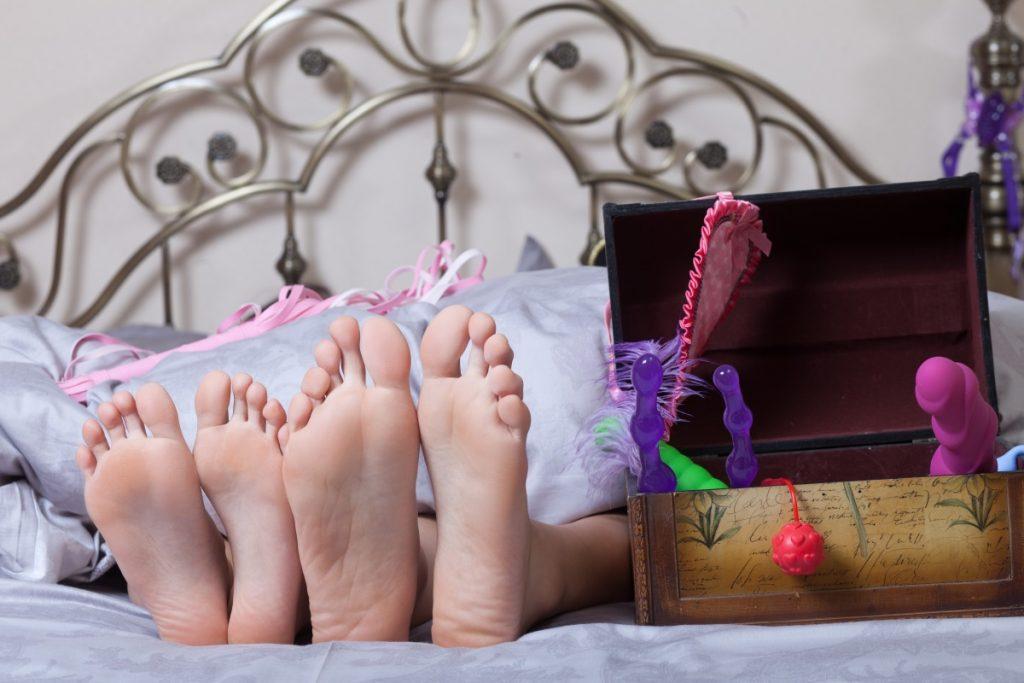 Pärchen im Bett mit Sex Toys